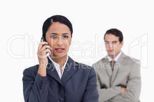 Saleswoman on her cellphone with colleague behind her