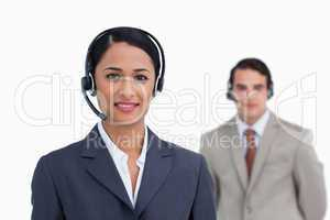 Smiling telephone support worker with colleague behind her