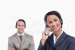 Smiling telephone support employee with co-worker behind her