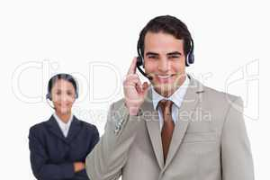 Smiling hotline employee with co-worker behind him