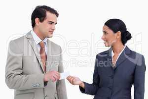 Saleswoman handing business card over to costumer