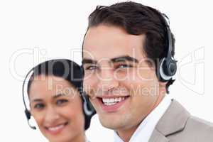 Close up side view of smiling call center agents at work