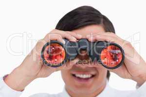 Close up of smiling young tradesman looking through binoculars