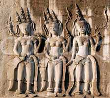 Three dancing apsara on the wall in Angkor Wat