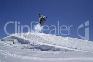 Snowboarder jumping in terrain park