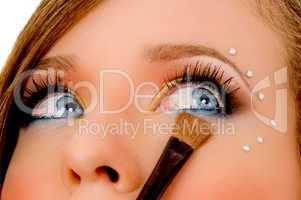 close view of young woman putting eyeliner