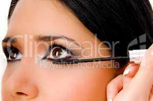 portrait of beautician applying maskara on woman's eye