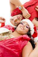 cheerful young couple wearing christmas hat lying down on floor