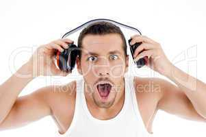 astonished male listening music on headphone
