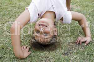 girl doing cartwheel in the grass