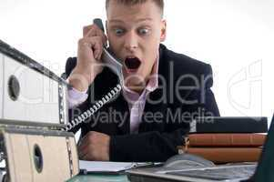 shocked businessman holding receiver