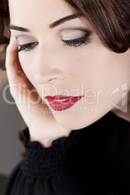 Closeup of a beautiful woman with red lips looking down