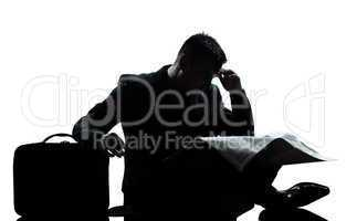silhouette man despair full length sitting reading newspaper