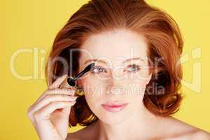 Glamorous Redhead Applying Mascara