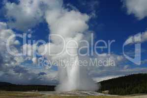 Old Faithful Geysir, blue sky and clouds, Yellowstone, Wyoming