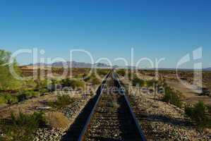 Railway track through vastness and emptiness of California desert
