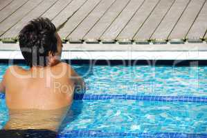 Young man relaxing at the edge of the swimming pool