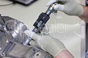 Mitarbeiter kontrolliert mit einer Innenmikrometerschraube die Bohrung in einem Getriebe Gehäuseteil