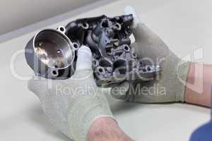 Mitarbeiter führt eine visuelle Kontrolle an einem Getriebe Gehäuseteil durch
