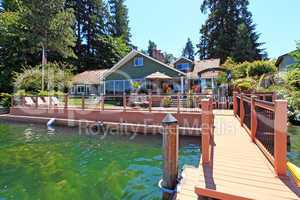 Lakefront green one story house with dock and large deck.