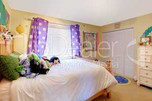 Baby girl room with toys and purple curtains.
