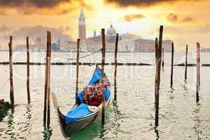 Gondola at sunset pier near in Venice, Italy