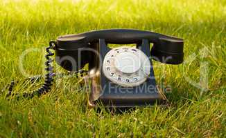Retro styled rotary telephone on grass
