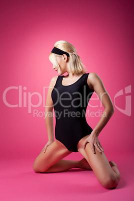 Sport woman in black swim body posing on pink