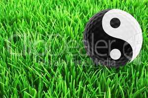 Golf-ball with Yin-Yang-Symbol on the fairway - golf wellness co