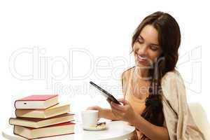 glückliche junge frau liest ebook an einem tisch mit büchern und kaffee