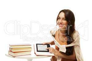 glückliche frau mit ebook und büchern sitzt an einem tisch