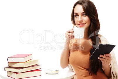 junge lächelnde frau mit kaffee und ebook sitzt an einem tisch