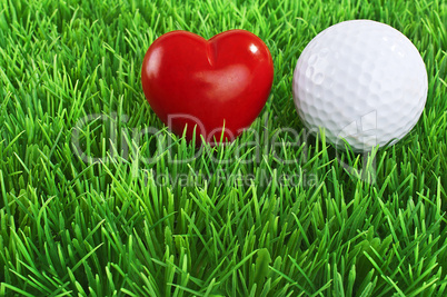 Red heart and white golf ball on the fairway