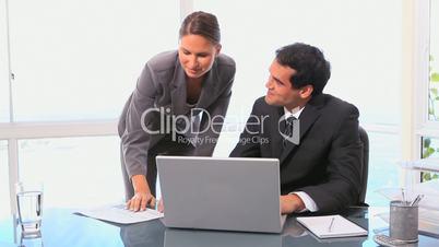 Geschäftsmann mit Kollegin am Schreibtisch