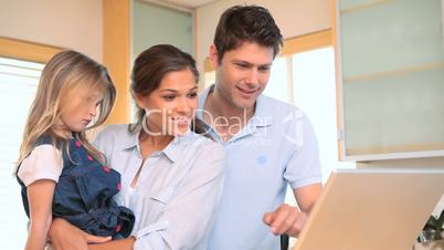 Junge Familie mit Laptop in der Küche
