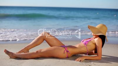 Junge Frau liegt im Sand