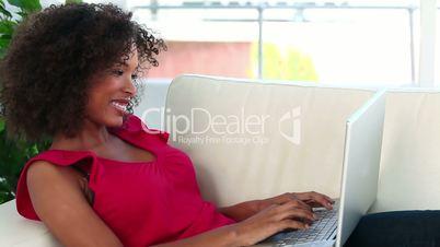 Frau mit Laptop auf einer Couch