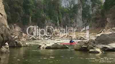 Adult man on red canoe paddling for fun among rocks