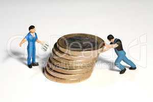 Miniatur Arbeiter schiebt Münzen