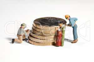 Miniatur arbeiter schweissen an einem Stapel Euro Münzen