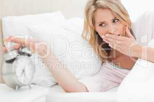 Woman reaching to silence alarm clock while glancing at the time