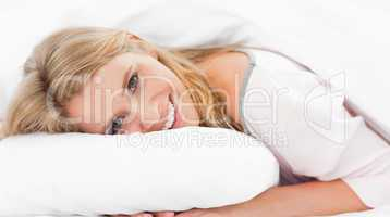 Woman lying in bed, her head on the pillow and eyes open while s