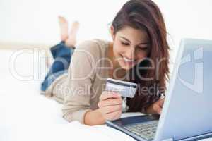 Smiling woman on her laptop reading her credit card details on t