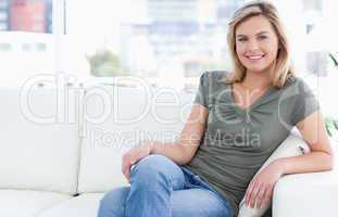 Woman sitting on the couch with crossed legs and a smile
