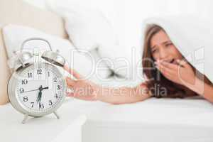 Woman yawning and reaching out for alarm clock from under her bl