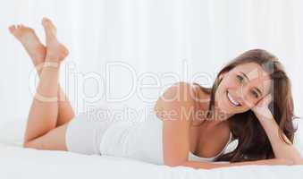 Woman lying on the bed, smiling, legs raised, and her head resti