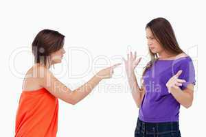 Teenage girl accusing her friend while pointing finger at her