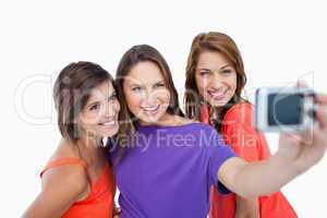 Three beautiful teenagers showing beaming smile in front of the