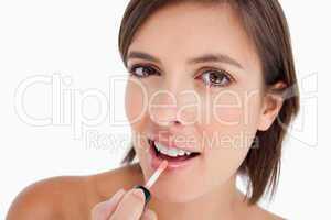 Beautiful teenager using a lip brush to apply lip gloss