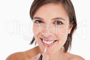 Teenager smiling while applying lip gloss with a lip brush